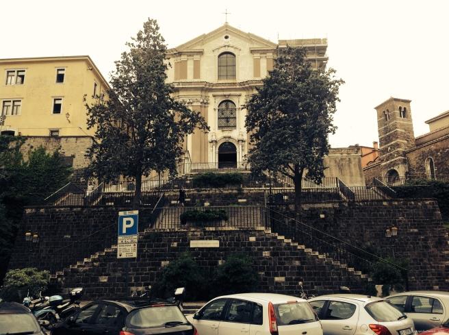 Ao centro, a igreja de Santa Maria Maggiore. O edifício amarelo é um convento e também a sede do instituto. À direita, a igreja mais antiga da cidade: a basílica de São Silvestre.