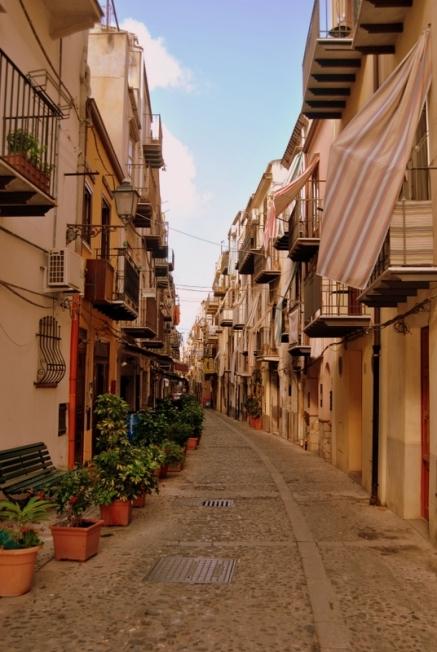 Um sinal de que estamos, muito provavelmente, na Sicília: as varandas cobertas com cortinas de riscas, a chamar a sombra fresca.